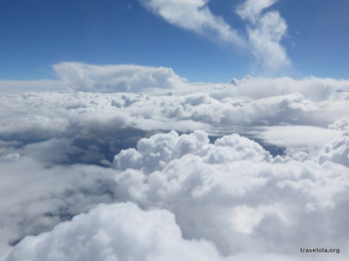 Looking out of a plane window at a blanket of fluffy clouds above Tasmania
