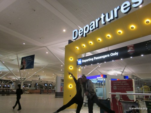 Finola Wennekes and Dane standing in front of a departures sign at Brisbane Airport