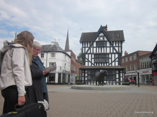 Tourists looking at a map in a square in Hereford, in front of a 17th century black and white building.