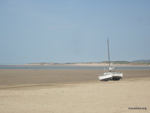 The quiet beach of Instow near Bideford in North Devon. Flat sand and a little sailing boat to the right. No people to be seen.
