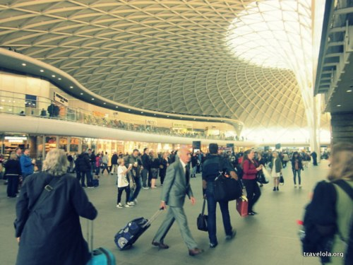 Kings Cross train station at rush hour. A business man walks across the frame pulling a suitcase.