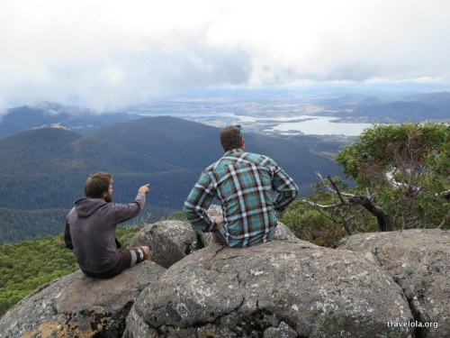 Two guys sitting on a rock up Mount Wellington overlooking the area surrounding Hobart.