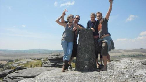 Four friends celebrating a climb up Roo Tor in Dartmoor, England