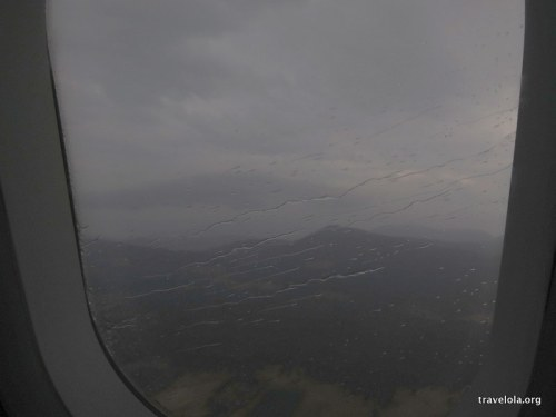 View from plane window on descent into Hobart. Grey skies and rain streaking across the window.